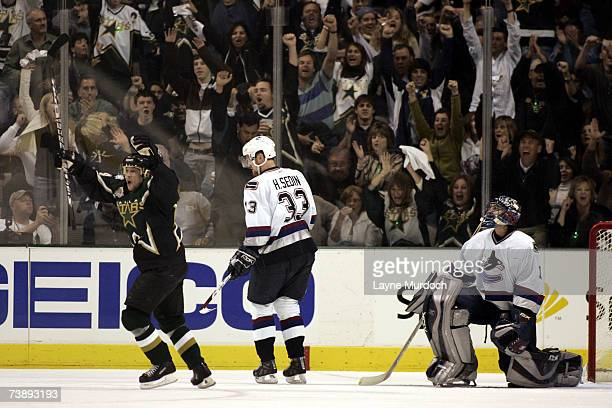 Stu Barnes of the Dallas Stars celebrates his goal against Roberto Luongo as Henrik Sedin of the Vancouver Canucks looks on during the 2nd period of...