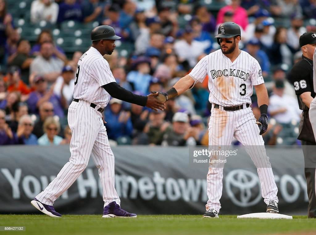 Stu Cole #39 of the Colorado Rockies congratulates Mike Tauchman #3 following a seventh-inning RBI triple against the Los Angeles Dodgers at Coors Field on October 1, 2017 in Denver, Colorado.