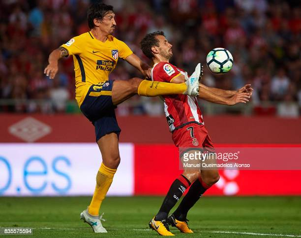 Stuani of Girona competes for the ball with Stefan Savic of Atletico de Madrid during the La Liga match between Girona and Atletico de Madrid at...