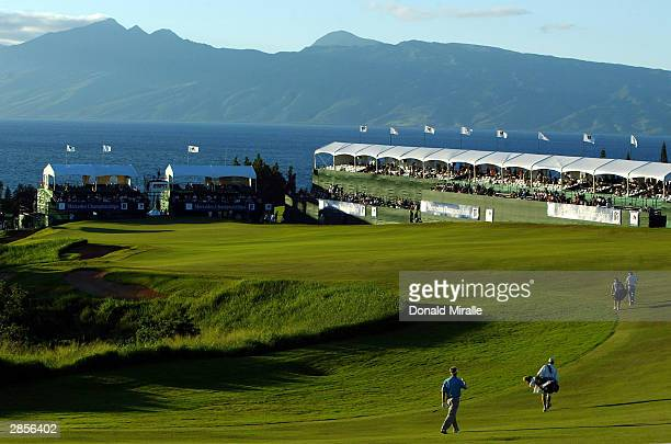 Stuart Appleby and Darren Clarke and their caddies make their way down the 18th fairway with Molokini in the background during the 2nd round of the...
