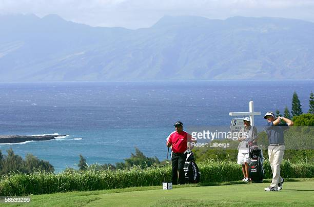 Stuart Appleby of Australia makes a tee shot on the 5th hole as Michael Campbell of New Zealand and Appleby's caddie Joe Damiano look on during the...