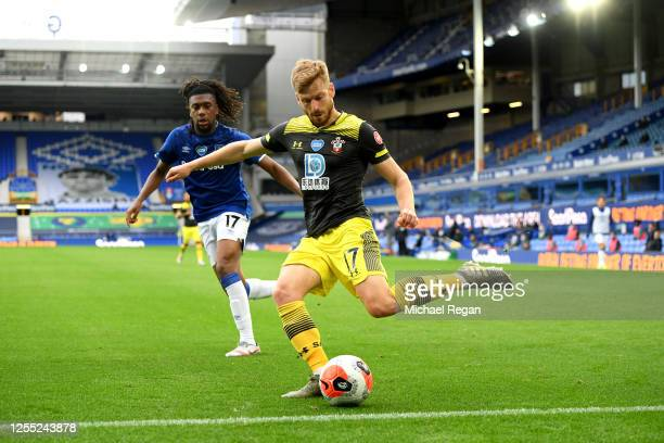 Stuart Armstrong of Southampton crosses the ball while under pressure from Alex Iwobi of Everton during the Premier League match between Everton FC...