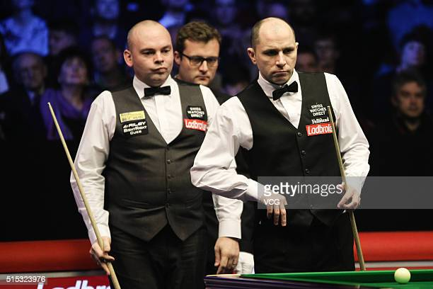 Stuart Bingham of England and Joe Perry of England react in the semifinal match on day five of the Ladbrokes World Grand Prix at Venue Cymru on March...