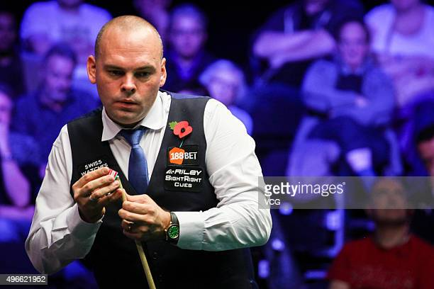 Stuart Bingham of England chalk his cue in Group Stage match against Zhou Yuelong of China on day 1 of Champion of Champions 2015 at Ricoh Arena on...