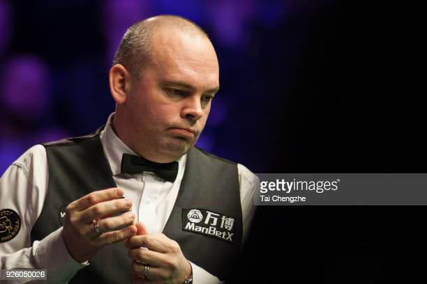 Stuart Bingham of England chalks the cue during his third round match against Matthew Stevens of Wales on day four of 2018 ManBetX Welsh Open at...