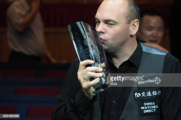 Stuart Bingham of England holds his trophy against Mark Allen of North Ireland during day seven of the World Snooker Bank of Communications OTO...