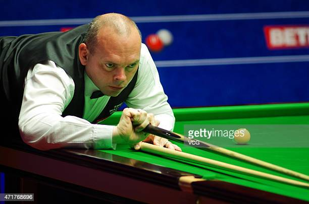 Stuart Bingham of England plays a shot against Judd Trump of England during the semifinal match on day thirteen of the 2015 Betfred World Snooker...