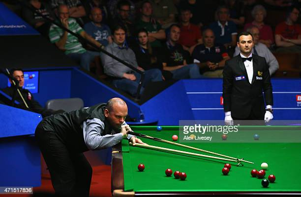 Stuart Bingham plays a shot against Ronnie O'Sullivan during day twelve of the 2015 Betfred World Snooker Championship at Crucible Theatre on April...