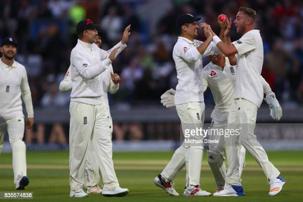 Stuart Broad of England celebrates with Alastair Cook after capturing the wicket of Jason Holder during day three of the 1st Investec Test match...