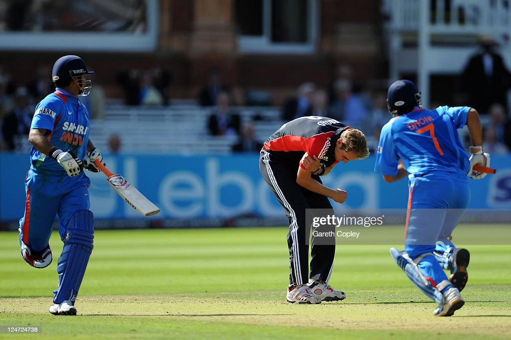 Stuart Broad of England holds his right arm as MS Dhoni (R) and Suresh Raina of India run between the wickets during the 4th Natwest One Day International match between England and India at Lord's Cricket Ground on September 11, 2011 in London, United Kingdom.