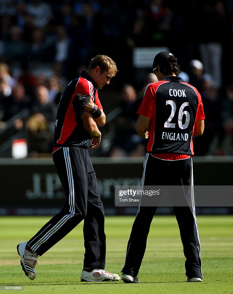 Stuart Broad (L) of England holds his right arm as he walks past Alastair Cook on his way to the pavilion during the 4th Natwest One Day International match between England and India at Lord's Cricket Ground on September 11, 2011 in London, United Kingdom.