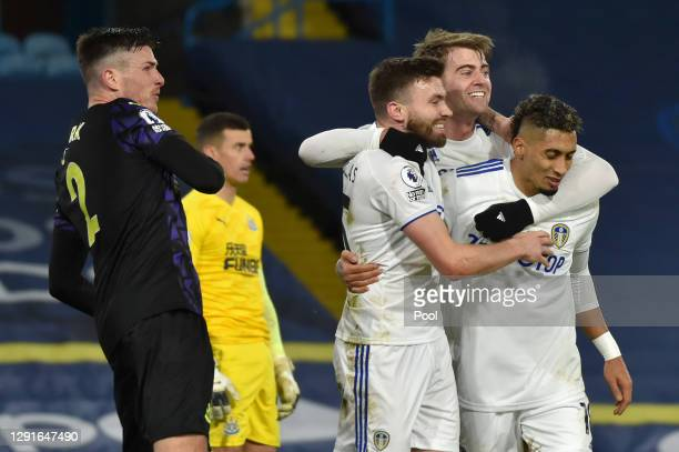 Stuart Dallas of Leeds United celebrates with teammates Patrick Bamford and Raphinha after scoring their team's third goal during the Premier League...