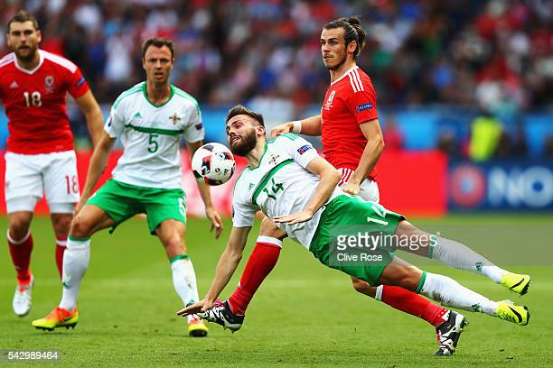 Stuart Dallas of Northern Ireland clears the ball in front of Gareth Bale of Wales during the UEFA EURO 2016 round of 16 match between Wales and...