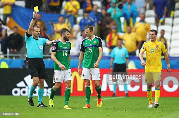 Stuart Dallas of Northern Ireland is shown a yellow card by Referee Pavel Kralovec during the UEFA EURO 2016 Group C match between Ukraine and...