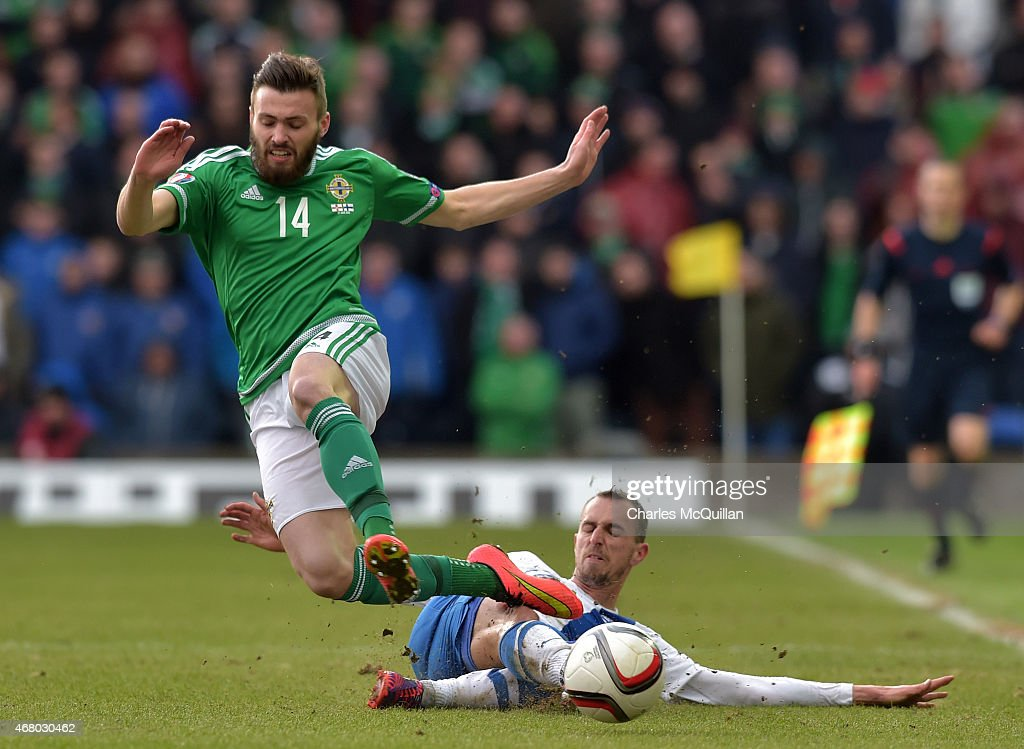 Stuart Dallas (L) of Northern Ireland is tackled by Sakari Mattila (R) of Finland during the EURO 2016 Group F qualifier at Windsor Park on March 29, 2015 in Belfast, Northern Ireland.