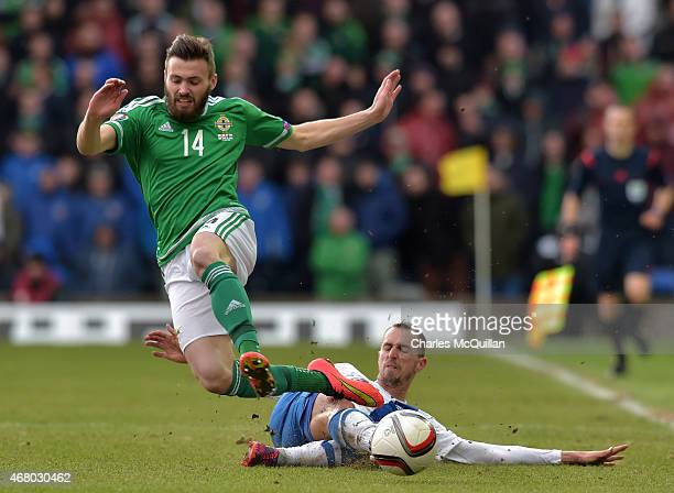 Stuart Dallas of Northern Ireland is tackled by Sakari Mattila of Finland during the EURO 2016 Group F qualifier at Windsor Park on March 29 2015 in...