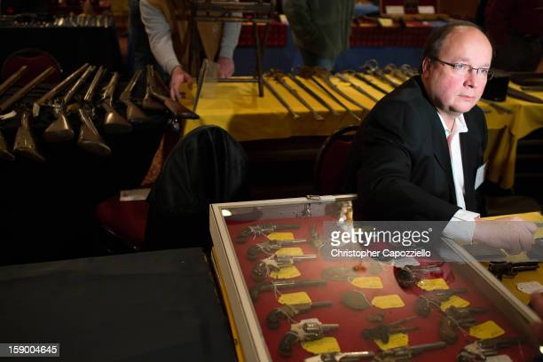 Stuart English of Milford New Hampshire sells antique guns at a gun show at the Crowne Plaza Hotel on January 5 2013 in Stamford Connecticut While...