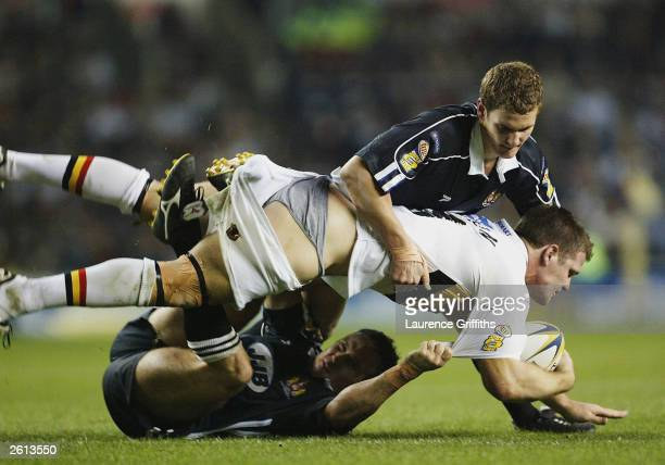 Stuart Fielden of Bradford is tackled by Sean O'Loughlin and Paul Johnson of Wigan during the Super League Grand Final match between Bradford Bulls...