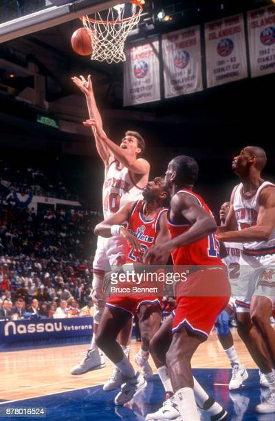 Stuart Gray of the New York Knicks shoots over Charles Jones and Albert King of the Washington Bullets during an NBA preseason game circa October...