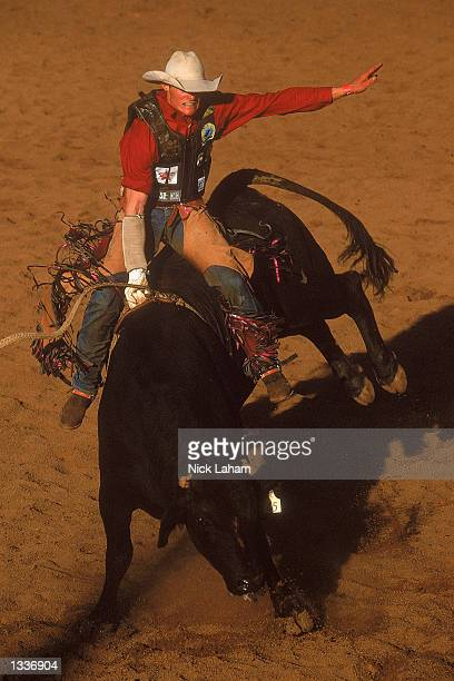 Stuart Hay rides in the Open Bull section during the Mount Isa Rodeo held in Mount Isa Australia on August 11 2002 The rodeo event held in the...