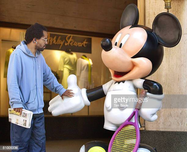 Stuart Jones touches the hand of a Mickey Mouse statue titled Love All designed by Andre Agassi on State Street June 28 2004 in Chicago Illinois This...