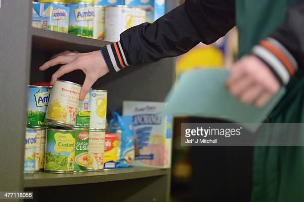 Stuart Little volunteer grabs to pack at a food bank on March 7 2014 in Whitburn Scotland Charities based in Scotland are reporting that many...