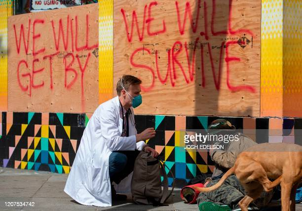 Stuart Malcolm, a doctor with the Haight Ashbury Free Clinic, speaks with homeless people about the coronavirus in the Haight Ashbury area of San...