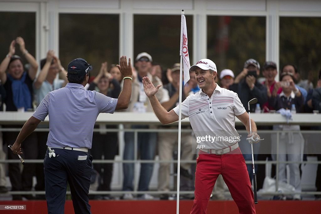 Stuart Manley (R) of Wales celebrates after reaching a play-off at the Hong Kong Open, high-fiving with Shiv Kapur (L) of India, at the Hong Kong Golf Club in Hong Kong on December 8, 2013. Miguel Angel Jimenez of Spain won the tournament.