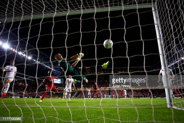 Stuart Moore of MK Dons makes a mistake as he tries to save a shot by James Milner of Liverpool which leads to a goal during the Carabao Cup Third...