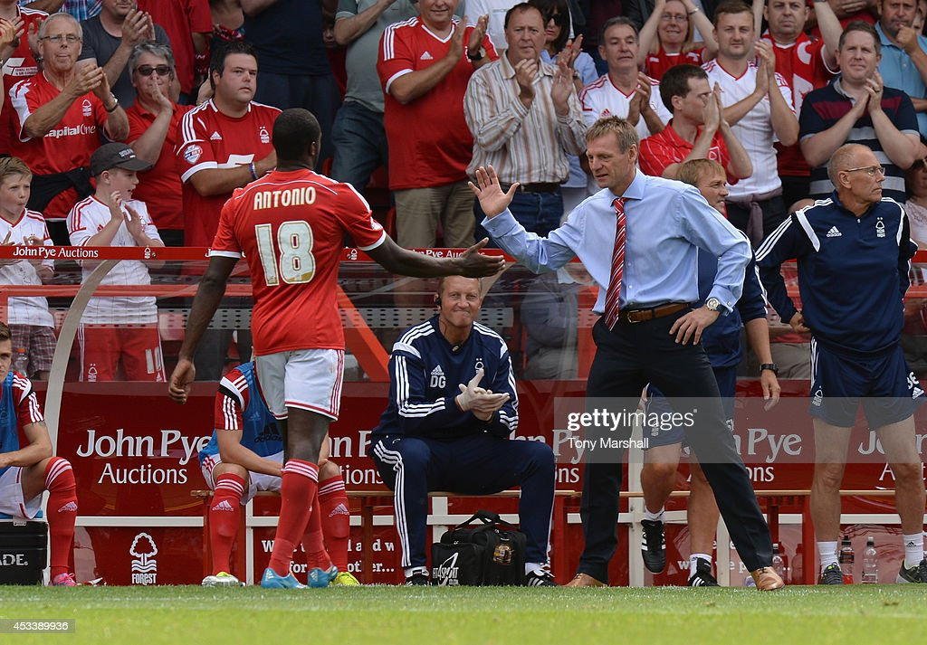 Stuart Pearce, Manager of Nottingham Forest shakes hands with Michail Antonio of Nottingham Forest during the Sky Bet Championship match between Nottingham Forest and Blackpool at City Ground on August 9, 2014 in Nottingham, England.