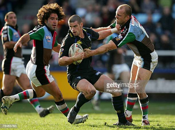 Stuart Reardon of Warrington Wolves is challenged by Scott Hill and Julien Rinaldi of Harlequins during the Engage Super League match between...