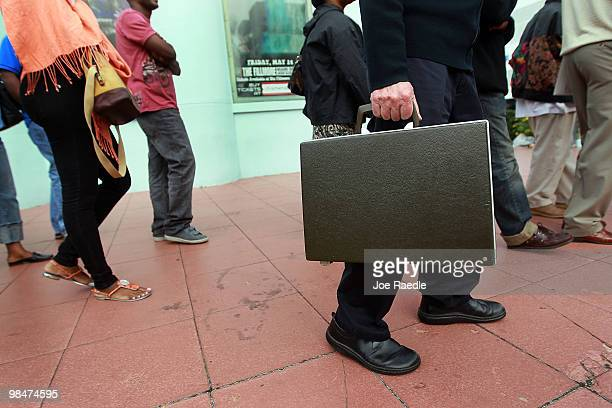 Stuart Scheckner holds his briefcase while waiting with others as he hopes for a chance to refinance his home mortgage loan with the Bank of America...