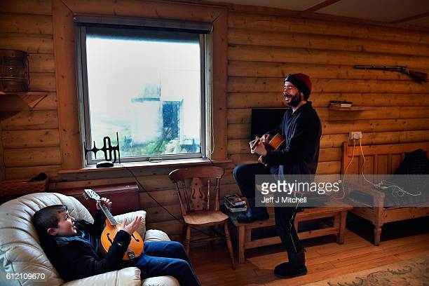 Stuart Taylor and Jack Smith the only school child on the Island of Foulaenjoy a quick tune on the guitar and mandolin on September 28 2016 in Foula...