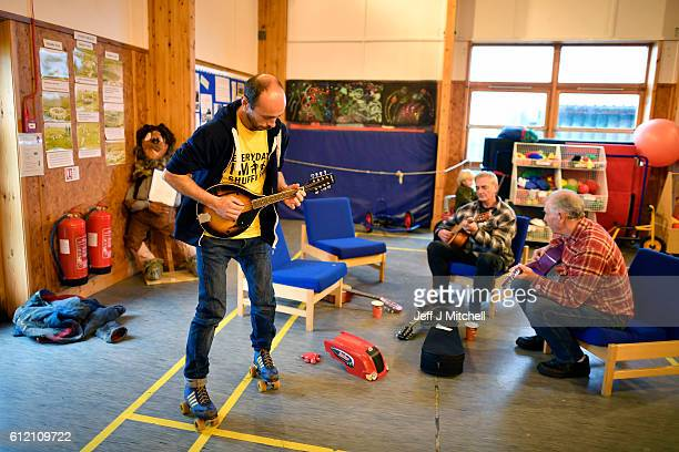 Stuart Taylor plays a tune while on roller skates with Davie Henry and Jim Grear at the primary school coffee morning on the Island of Foula on...