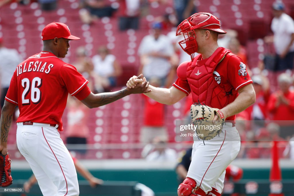 Stuart Turner #32 of the Cincinnati Reds congratulates Raisel Iglesias #26 after the final out in the ninth inning against the New York Mets at Great American Ball Park on August 31, 2017 in Cincinnati, Ohio. The Reds defeated the Mets 7-2.