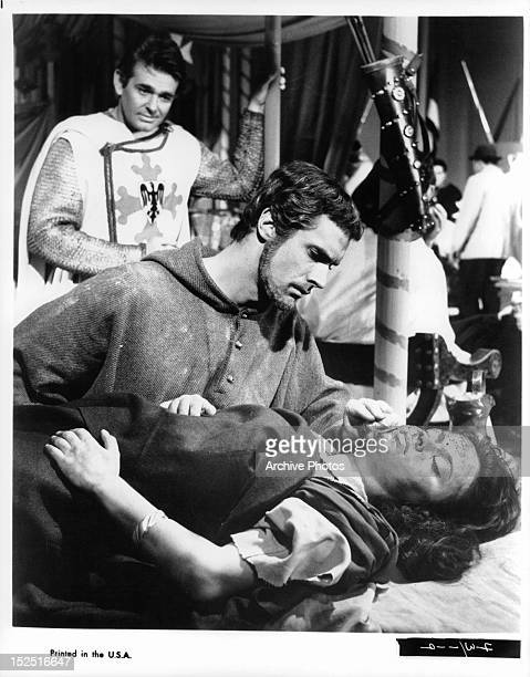 Stuart Whitman in background as Bradford Dillman looks over fallen woman in a scene from the film 'Francis Of Assisi' 1961