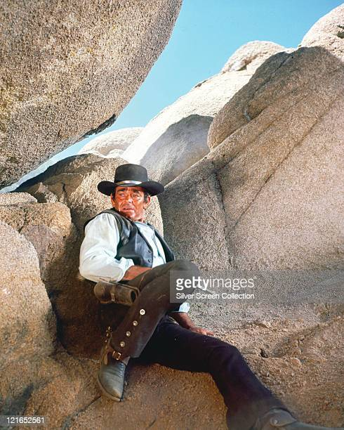Stuart Whitman US actor wearing a black cowboy hat and western costume as he sits nervously against rocks in a publicity still issued for the US...