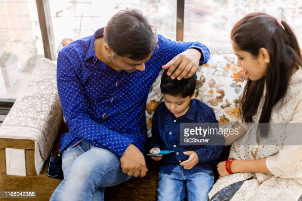 stubborn kid does not want to give up playing on the smartphone - stubborn stock pictures, royalty-free photos & images