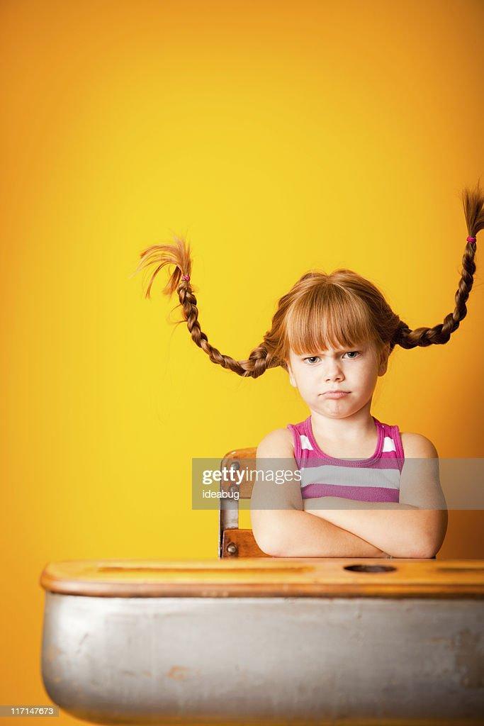Terquedad niña de pelo roja con brazos cruzados en la escuela escritorio : Foto de stock