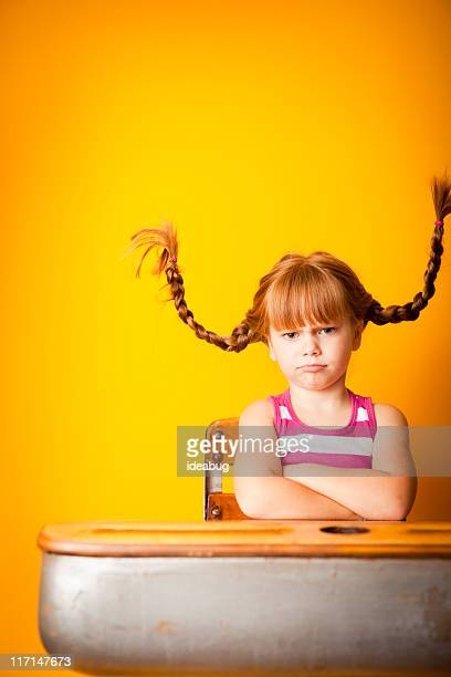 Stubborn Red-Haired Girl with Arms Crossed in School Desk