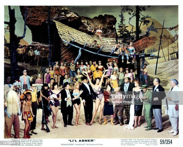 Stubby Kaye, Leslie Parrish, Julie Newmar, and townspeople gather in a scene from the film 'Li'l Abner', 1959.