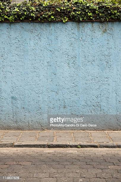 Stucco wall along cobblestone street