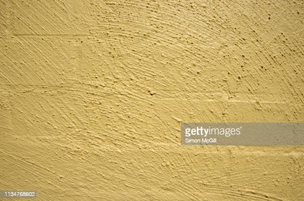 stucco-covered brick wall painted yellow - off white stock pictures, royalty-free photos & images