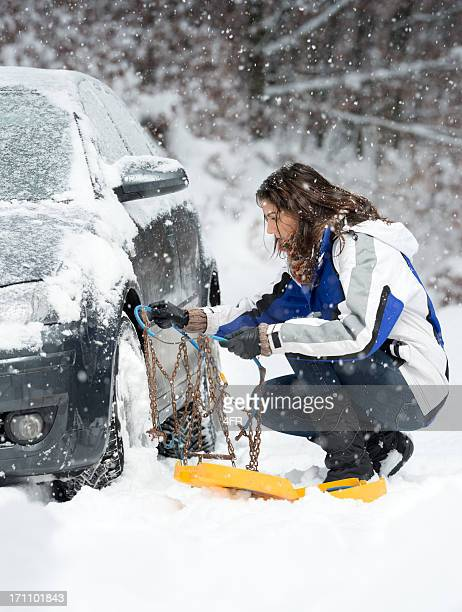 Stuck in a Blizzard, Woman applying Snow Chains