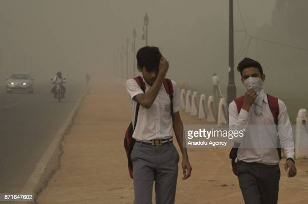 Studenrs covering their faces with a handkerchiefs walk as the air pollution hit the record level hazardous in Delhi India on November 08 2017 Chief...
