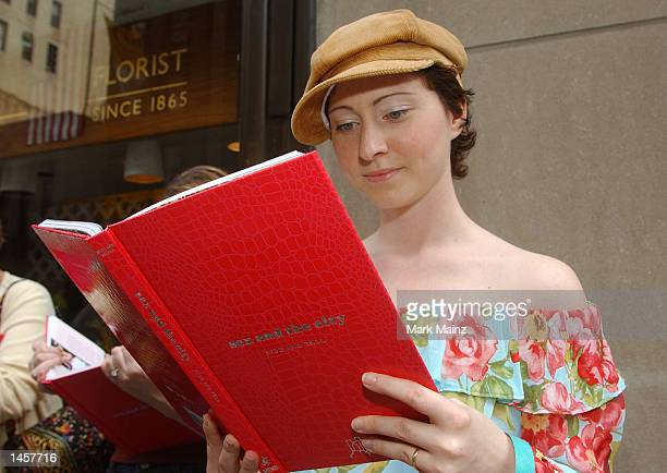 Student Adriana Reali from Cologne Germany reads a copy of 'Sex and the City Kiss and Tell' while waiting in line to get her book signed October 3...