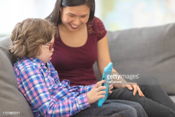student and his tutor using a tablet together - assistive technology stock photos and pictures