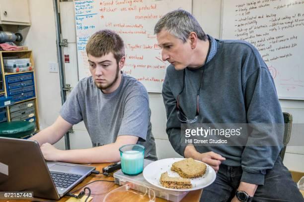 Student and teacher using laptop near whiteboard