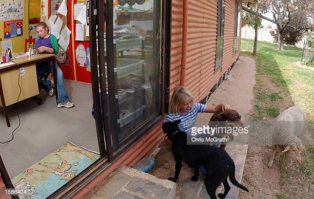 Student Anna Jackson speaks to her teacher during her reading lesson on their property three hours from Broken Hill on October 24 2002 in New South...