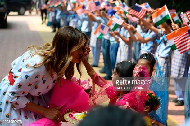 A student applies vermilion powder on the forehead of US First Lady Melania Trump as she arrives at Sarvodaya CoEd Senior Secondary School in New...